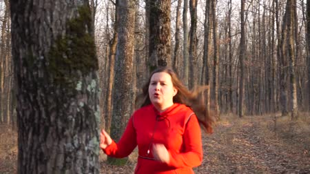 motivováni : Motivated fat girl in red runs through the autumn forest.Stops to relax