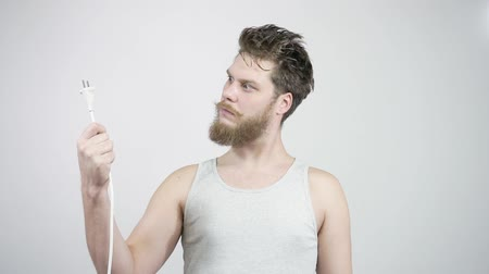 шок : The bearded guy looks at the cable plug. Surprise home electrician