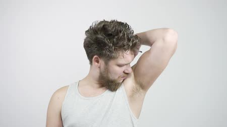 dezodorant : Young bearded man sniffing his armpit, something stinks very bad