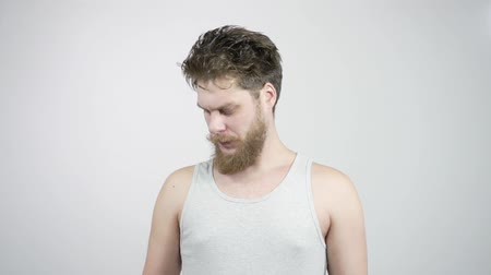 unpleasant smell : Young bearded man sniffing his armpit, something stinks very bad