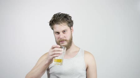 酔った : Drunk bearded guy drinking light beer and kicks the taste