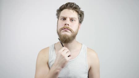 beard trim : The guy combing his thick beard looking in the mirror
