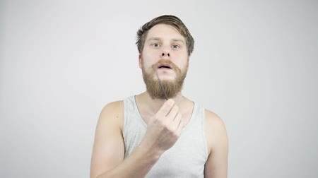 trimmelés : The guy combing his thick beard looking in the mirror