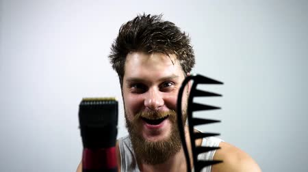 урод : Unshaven bearded guy holding a comb and a clipper.To get a haircut or not