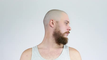 строгий : The bearded guy turns and stares into the camera. Bald head