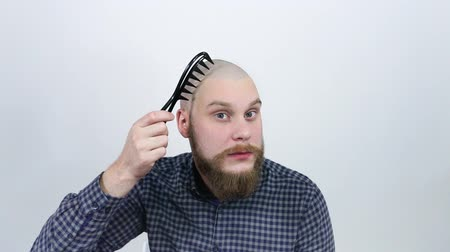 hair growth : A young man with a red beard, combing his bald head with a large tooth comb.