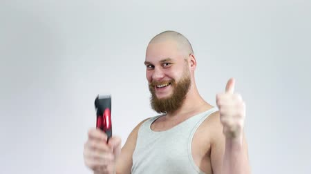 navalha : Bald guy with a beard and a clipper in his hands, shaving himself.Thumbs up