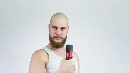 beard trim : Bald guy with a beard and a clipper in his hands, shaving himself.Thumbs up