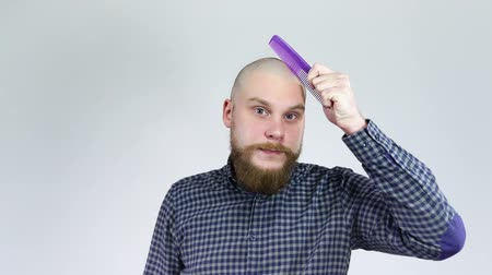 hair growth : Smiling bearded man in shirt and combing his bald head purple comb