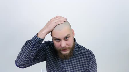 shaver : A man examines his bald head in the reflection and experiencing from hair loss