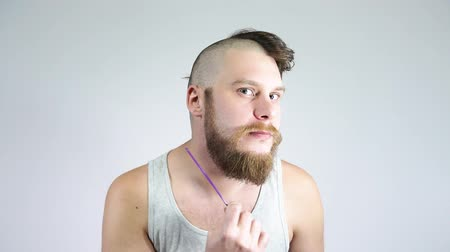 esvoaçantes : The guy combing his beard with a comb. Half shaved hair on his head. Stock Footage