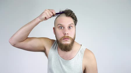 Hair and bald.The bearded guy brushing her hair and looking in the mirror. Stock mozgókép