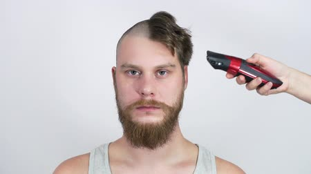 hair growth : Haircut bald clippers. The bearded man looks while he cut.