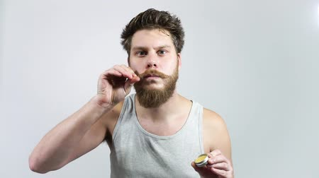 Wax for the care of the beard.A man puts his mustache with wax.Mens cosmetics Stock mozgókép