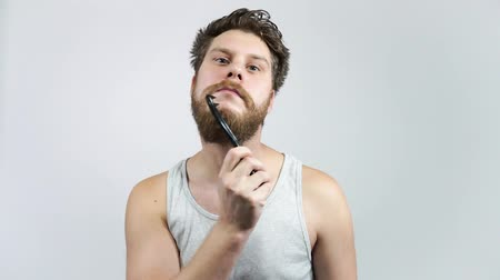 esvoaçantes : Man combing his beard. Hipster guy Brushing his ginger beard. Stock Footage