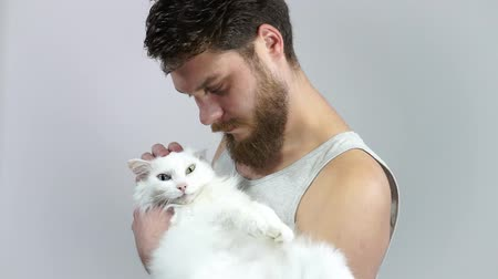 The bearded guy is holding his beloved pet. Favorite cat with different eyes.