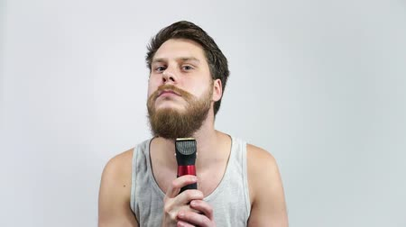 Grooming The Beard. The man trims his beard with clippers in the bathroom.