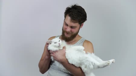 A bearded man kissing a white cat. Love pet and owner. Heterochromia. Stock mozgókép