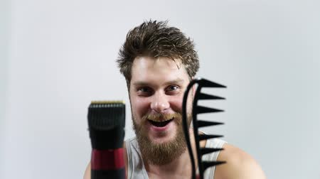 What hairstyle to choose? To shave or not? A man holding a comb and a clipper.