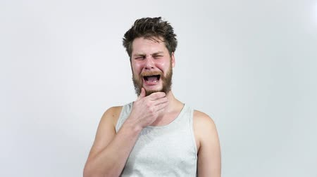 The man with the beard crying.A young guy cries and tries.