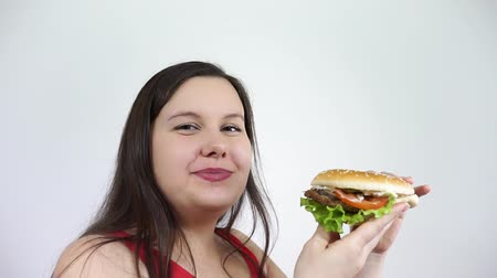 A young woman with obesity to eat a hamburger and feel the joy. Fast food, junk. Stock mozgókép