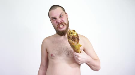 кусаться : A man stands with a fried chicken leg and then eats her.Turkey meat. Стоковые видеозаписи