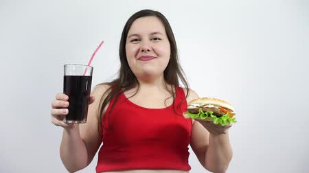 Plus size girl eating Burger and drinking coke. Fast food, overweight, obesity.
