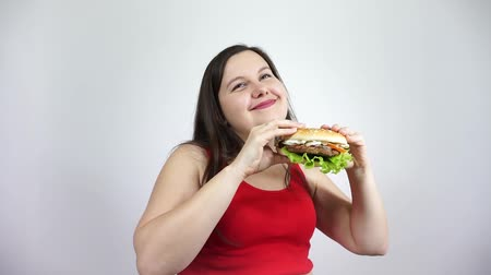Fat girl eating a hamburger. Overweight woman in red eating fast food. Obesity.