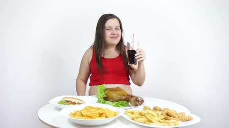 Overweight girl looking at the food and smiles. Unhealthy junk food, obesity. Stock mozgókép
