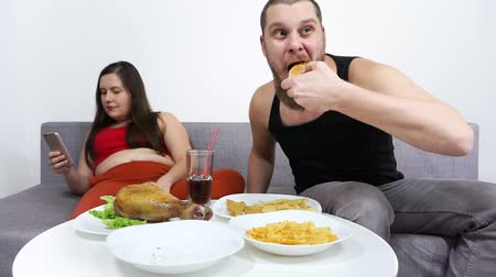 Overweight couple eating fast food, hamburger, chips, french fries and watch TV. Stock mozgókép