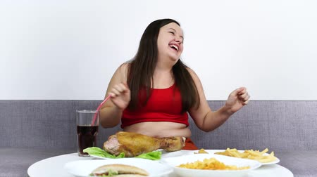 Plump cheerful woman dancing and smiles. Overweight woman eating hamburger.