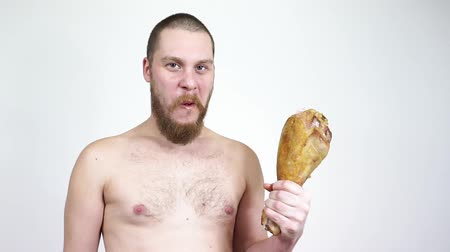 The bald guy with a beard eating a Turkey leg.Aggressive hungry man. Stock mozgókép
