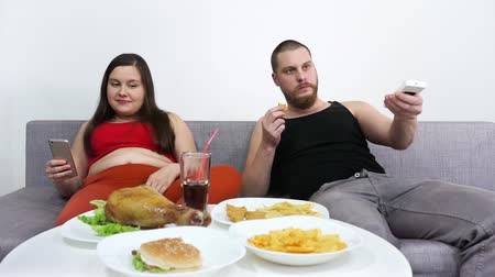 coque : Fat girl using mobile phone. Guy watches TV. Bad family relationships.