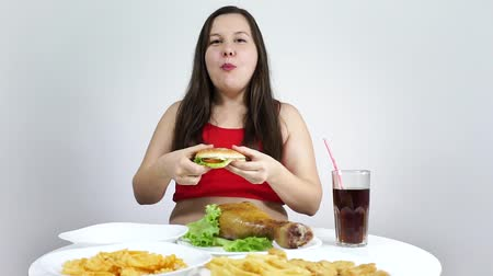 kola : Overweight woman eating fast food..Harmful food, obesity.