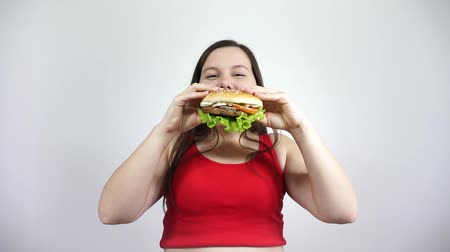 Unhealthy Eating. Happy fat girl eating a Burger and smiles. Stock mozgókép