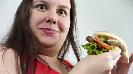 Overweight woman eating hamburger. Overeating fast food and obesity.