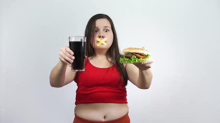 Diet.Young woman with duct tape over her mouth, preventing her to eat junk food. Stock mozgókép