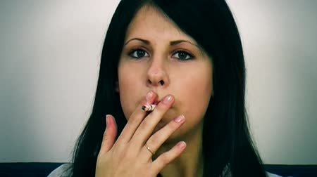 cigarettes : Young woman smokes close to the camera