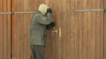 güvenli : Robber trying to break the garage door Stok Video