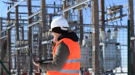site :  Electrician with computer near the electricity substation Stock Footage