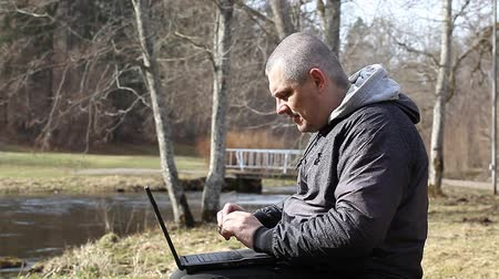 payment : Man with cell phone and PC on a bench in the park