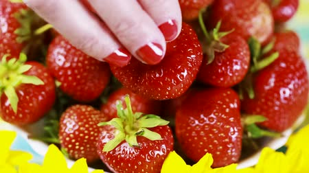 unha : Womans hand puts a strawberry