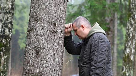 be sad : Depressed man leaning on a tree episode 1 Stock Footage