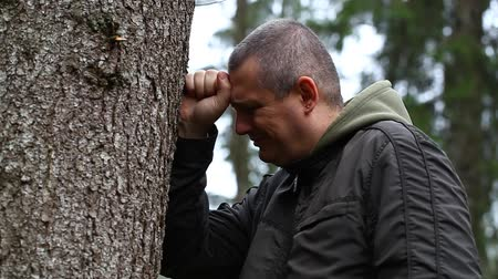 be sad : Depressed man leaning on a tree episode 2 Stock Footage