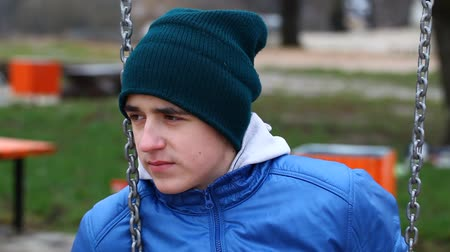 smutek : Sorrowful teenage boy swinging in the park episode 1