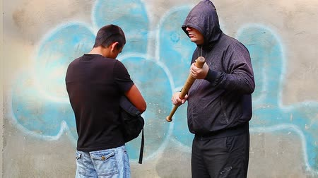 насилие :  Aggressive man with a baseball bat talking with teenager