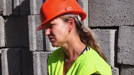 perigoso : Worried woman-builder dressed in helmet and vest