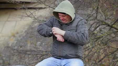 itch : Man with itchy arm at outdoors on the bench Stock Footage