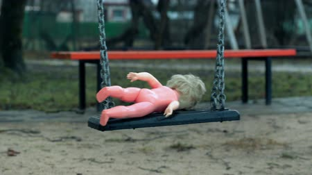 boneca : Old abandoned doll on a swing at outdoors