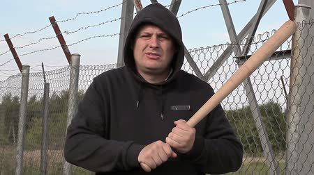 płot : Aggressive man with baseball bat near wire fence